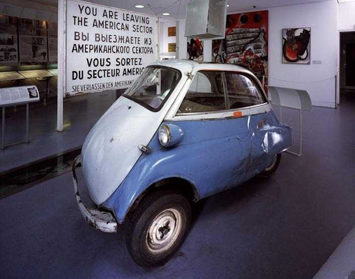 """<p>The <a href=""""https://www.bmw.com/en/automotive-life/history-BMW-isetta.html"""" rel=""""nofollow noopener"""" target=""""_blank"""" data-ylk=""""slk:BMW Isetta"""" class=""""link rapid-noclick-resp"""">BMW Isetta</a>, better known as the 'bubble car' was a 1950's design classic. Just seven and a half feet long, it took 30 seconds to get up to 30 mph from a standing start. Far too small to smuggle a hidden passenger out under the eyes of the border guards–unless you were a very smart mechanic. </p><p>In 1963, Klaus-Günter Jacobi <a href=""""https://www.bmw.com/en/automotive-life/berlin-wall-escapes-in-a-bmw-isetta.html"""" rel=""""nofollow noopener"""" target=""""_blank"""" data-ylk=""""slk:converted his Isetta"""" class=""""link rapid-noclick-resp"""">converted his Isetta</a> over several weeks, moving the storage box behind the seat up four inches and welding it back in place, removing the air filters and spare tire to make more space, replacing the rule tank with one the size of an old can, bending the exhaust pipe – then sanding it all down and leaving no trace. Then 5-foot-7-inch Manfed Koster could just squeeze into the hiding space. The border guards did not bother checking such a tiny vehicle, and Jacobi drove right through with his concealed passenger.</p>"""