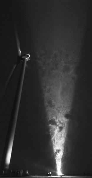 Traces of vortices shed from the turbine hub and tower behind a 2.5 MW wind turbine are visualized by the snowflakes illuminated in a light sheet parallel to the wind direction.