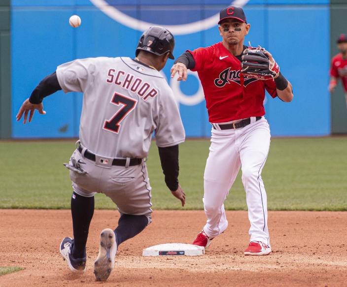 Cleveland Indians' Andres Gimenez forces Detroit Tigers' Jonathan Schoop at second base and throws to first to complete a double play during the fourth inning of a baseball game in Cleveland, Sunday, April 11, 2021. (AP Photo/Phil Long)