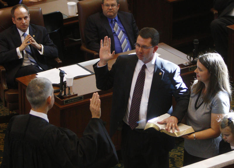 Oklahoma state Rep. Kris Steele, R-Shawnee, center, is sworn in as Speaker of the Oklahoma House, with his wife, Kellie, right, at his side, in Oklahoma City, Tuesday, Jan. 4, 2011. At left is Oklahoma Supreme Court Chief Justice Steven W. Taylor. (AP Photo/Sue Ogrocki)