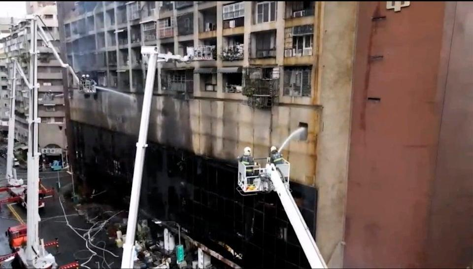 Firefighters jet water into the building (AP)
