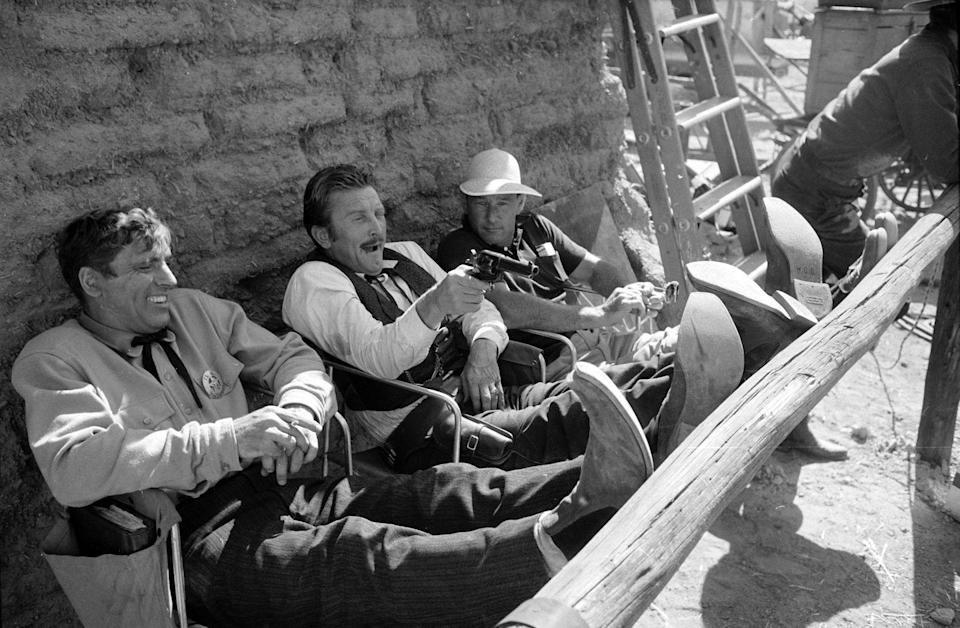 <p>While taking a break from filming <em>Gunfight at the O.K. Corral,</em> Douglas practices taking aim with his prop gun and chats with his costars, Burt Lancaster and John Sturges. </p>