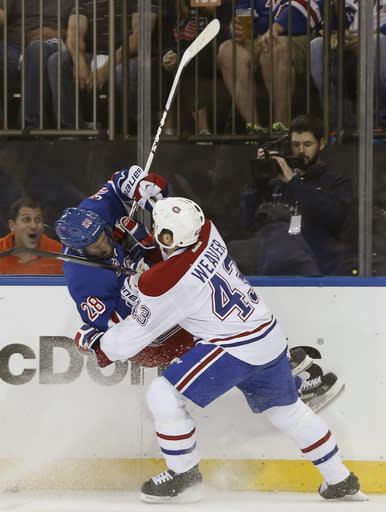 Montreal Canadiens defenseman Mike Weaver (43) checks New York Rangers center Dominic Moore during the second period of Game 4 of the NHL hockey Stanley Cup playoffs Eastern Conference finals, Sunday, May 25, 2014, in New York. (AP Photo/Kathy Willens)