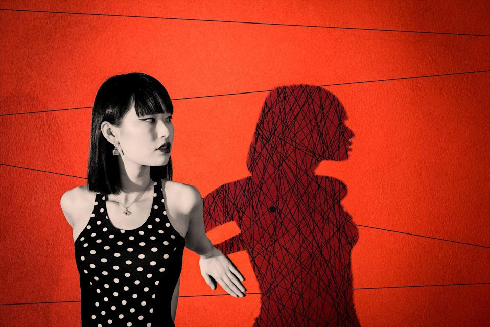 What Is Shadow Work? Young woman leaning against red wall, creating dramatic shadow with scribbles inside