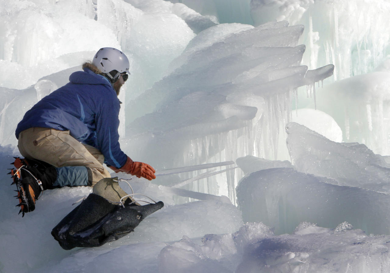 In this photo taken Wednesday Jan. 8, 2014 Cory Livingood places icicles on the top of his ice castle at the base of the Loon Mountain ski resort in Lincoln, N.H. The ice castle begins to grow in the fall when the weather gets below freezing and thousands of icicles are made and harvested then placed around sprinkler heads and sprayed with water. The castle will continue to grow as long as the temperatures stay below freezing. (AP Photo/Jim Cole)