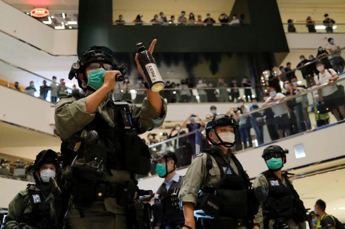 A riot police wearing face mask to avoid the spread of the coronavirus disease (COVID-19) holds a pepper spray as he tries to disperse anti-government protesters as they stage a rally at a shopping mall, in Hong Kong