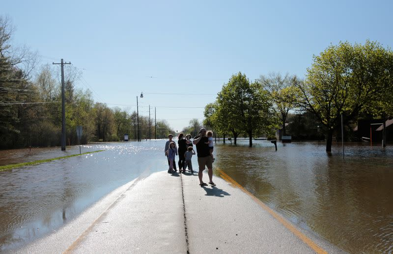 Residents look at a partially submerged street along the Tittabawassee River, after two dam failures submerged parts of Midland, Michigan