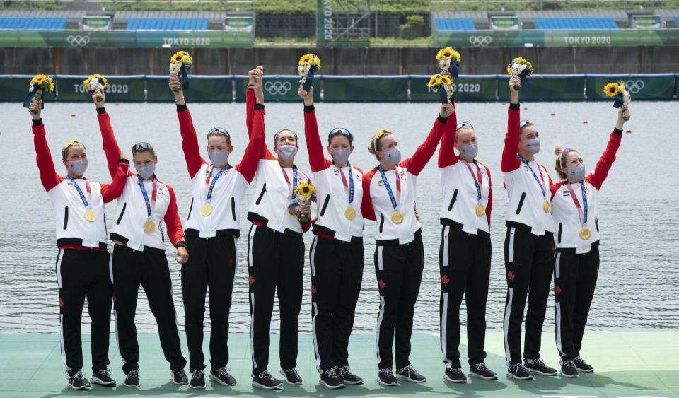 """<span class=""""caption"""">Canada's Lisa Roman, Kasia Gruchalla-Wesierski, Christine Roper, Andrea Proske, Susanne Grainger, Madison Mailey, Sydney Payne, Avalon Wasteneys and Kristen Kit celebrate on the podium after winning the gold medal in women's eight rowing competition at the Tokyo Olympics.</span> <span class=""""attribution""""><span class=""""source"""">THE CANADIAN PRESS/Adrian Wyld </span></span>"""