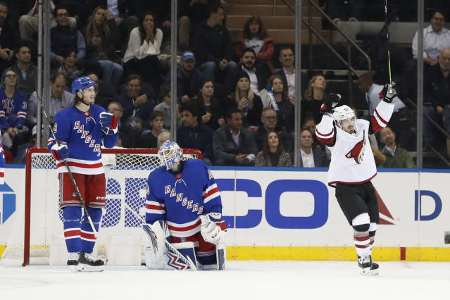 Arizona Coyotes right wing Conor Garland (83) celebrates a goal scored by Alex Goligoski, not shown, on New York Rangers goaltender Alexandar Georgiev, middle, during the second period of an NHL hockey game Tuesday, Oct. 22, 2019, in New York. Rangers left wing Brendan Lemieux is at left. (AP Photo/Kathy Willens)