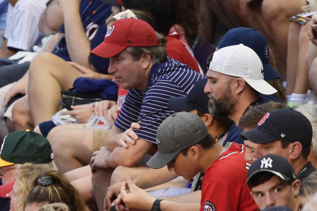 CORRECTS SPELLING TO KAVANAUGH, INSTEAD OF KAVANUAGH - Supreme Court nominee Judge Brett Kavanaugh, in red hat, sits in the stands before the Major League Baseball All-star Game, Tuesday, July 17, 2018 in Washington. (AP Photo/Susan Walsh)