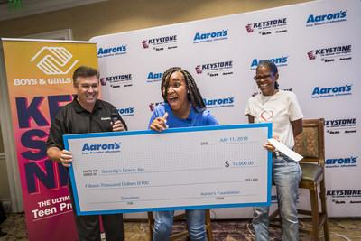 """14-year-old Serenity Gary and her grandmother, 58-year-old Karlette """"Koko"""" Karras, receive a surprise $15,000 check from Mike Dickerson, VP of Corporate Communications & Investor Relations at Aaron's, Inc., at the Boys & Girls Clubs of America's 52nd National Keystone Conference presented by Aaron's, Inc.. The donation is for her charity Serenity's Grace, which fights homelessness and hunger in the Orlando area. (Roberto Gonzalez/AP Images for BGCA)."""