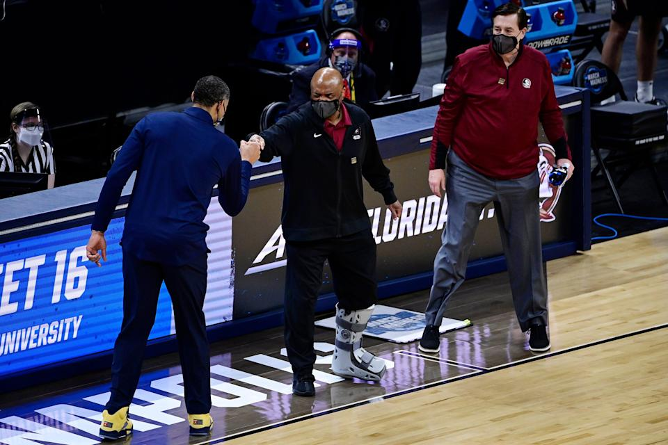 Florida State head coach Leonard Hamilton, center, fist bumps Michigan head coach Juwan Howard, left, following the Wolverines' victory in the Sweet 16.