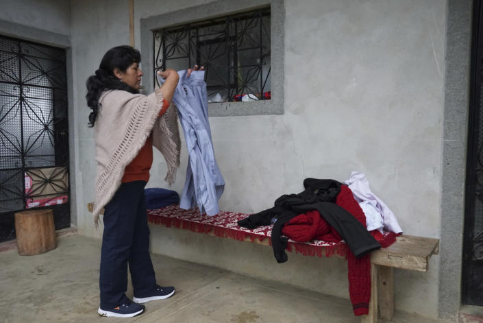 The future first lady of Peru, Lilia Paredes, 48, folds a shirt that belongs to her husband as she packs her family belongings, in the courtyard of her home in Chugur, Peru, Thursday, July 22, 2021. Her husband, leftist Pedro Castillo catapulted from unknown to president-elect with the support of the country's poor and rural citizens, many of whom identify with the struggles the teacher has faced. (AP Photo/Franklin Briceno)