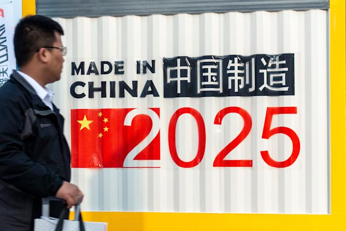 """A man passes a symbol reading """"Made in China 2025"""" during a 2018 manufacturing expo in Shanghai. (Photo: VCG/VCG via Getty Images)"""
