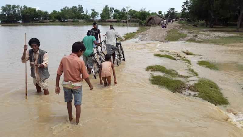 In this photograph taken on August 16, 2014, Nepalese villagers walk through floodwaters in Banke District some 351kms (218 miles) west of Kathmandu (AFP Photo/)