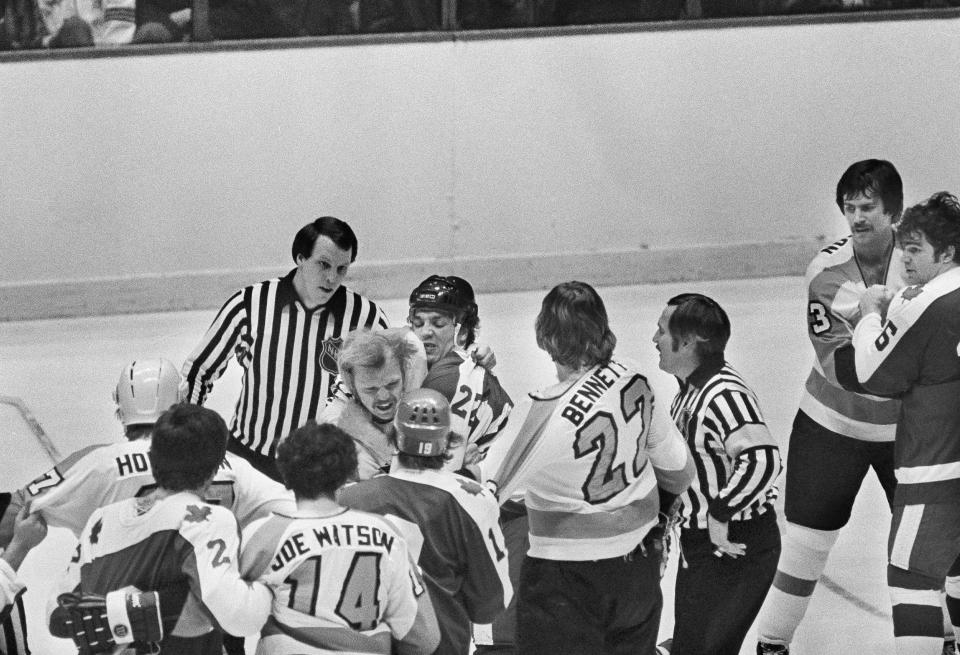 FILE - In this March 8, 1977, file photo, Philadelphia Flyers Bob Kelly, left, and Dave Williams (22) of the Toronto Maple Leafs fight in the first period, before both drawing penalties of five minutes for fighting and Williams a game misconduct that sent him to the showers, during an NHL game in Philadelphia. In the 1970s, the Flyers had guys like Dave The Hammer Schultz, Bob The Hound Kelly and Andre Moose Dupont around to not just beat opponents but beat them up, too. More than 40 years later, the Flyers still carry the Bullies nickname but are hardly bullying anyone: Theyre one of only two teams in the NHL without a fight a quarter of the way through the season. (AP Photo/Bill Ingraham, FIle)