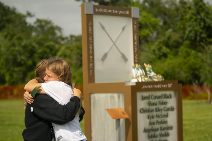 """Chailyn Gillespie, who is graduating from Santa Fe High School this year, hugs a friend next to the new memorial to the ten victims of the 2018 shooting at the high school, following a dedication ceremony, Tuesday, May 18, 2021, outside of the high school in Santa Fe. The Santa Fe Ten Memorial Foundation unveiled the """"Unfillable Chair,"""" a student designed memorial, on the third anniversary of the shooting. The foundation is planning a larger memorial for the future. (Mark Mulligan/Houston Chronicle via AP)"""