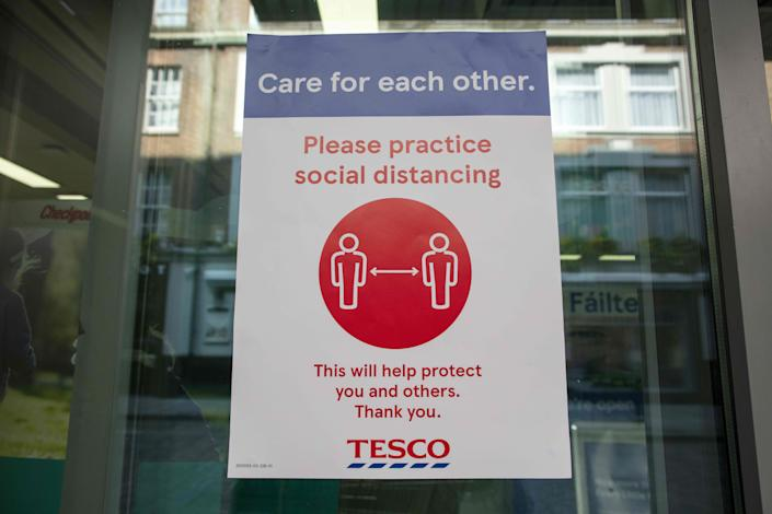 """A sign outside a branch of a Tesco supermarket alerts customers for the need to obey social distancing measures, in Dublin, on March 25, 2020, after Ireland introduced measures to help slow the spread of the novel coronavirus. - Ireland's prime minister Leo Varadkar on Tuesday announced that all non-essential businesses will shut from midnight as part of the country's latest measures to tackle the coronavirus outbreak. """"These are unprecedented actions to respond to an unprecedented emergency,"""" he said, adding the measures would remain in place until at least April 19. (Photo by PAUL FAITH / AFP) (Photo by PAUL FAITH/AFP via Getty Images)"""