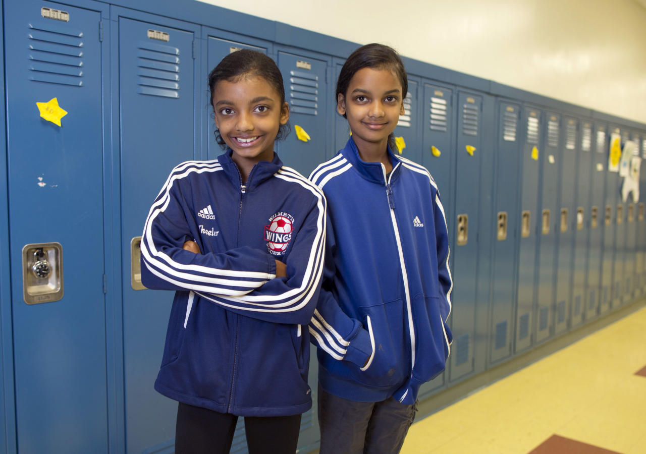 In this Thursday, June 6, 2013 photo, Summer Gaines-Wheeler, left, and her twin sister, Sydney, one of the 24 sets of twins from Highcrest Middle School in Wilmette, Ill., pose for a portrait in Wilmette, Ill. The group is attempting to break a Guinness Book of World Records for the amount of twins in one grade which is currently 16 sets. (AP Photo/Scott Eisen)