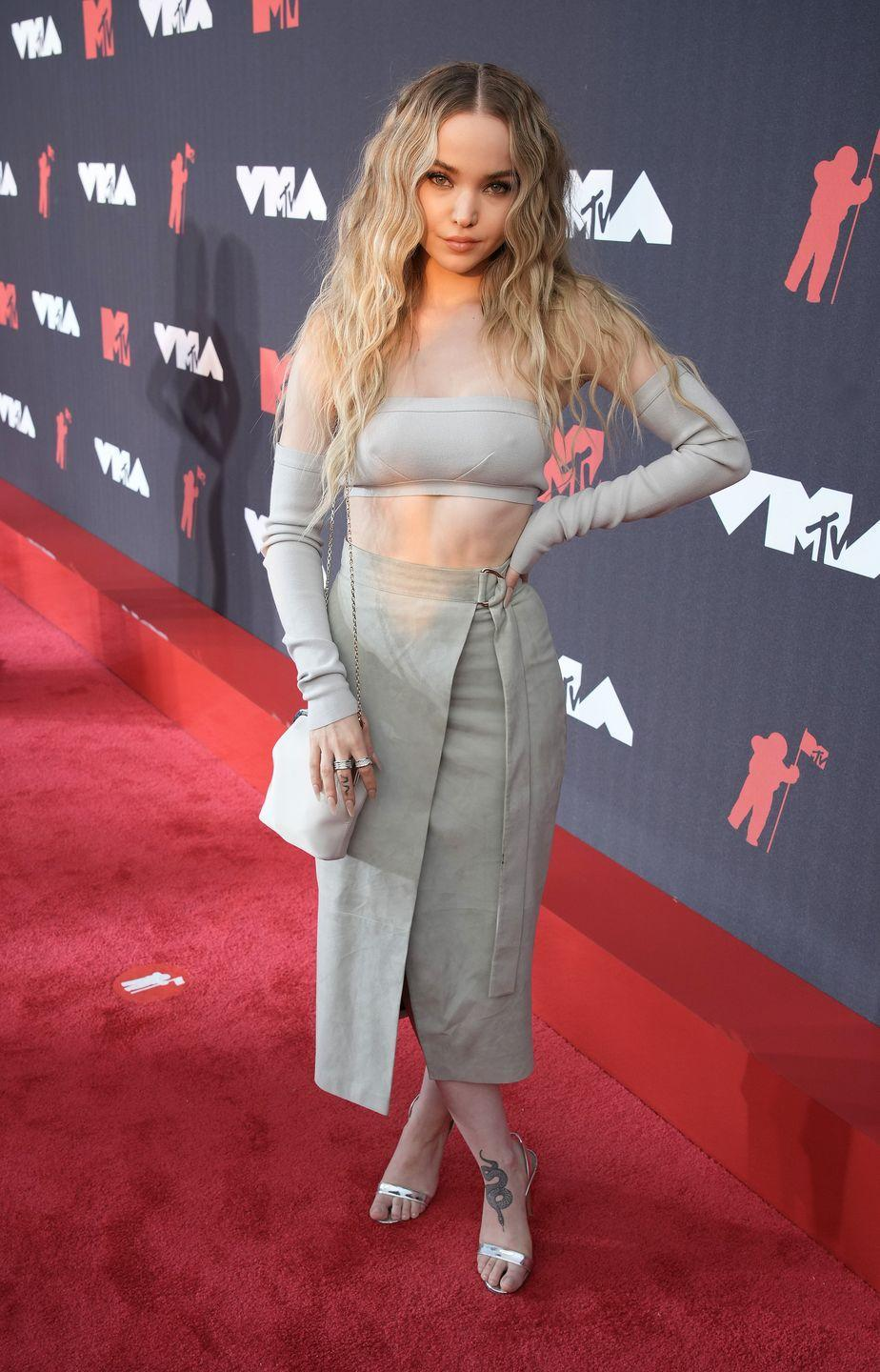 <p>Dove Cameron appeared on the carpet in an all-gray ensemble featuring a bandeau top, midi skirt, gloves and a matching off-the-shoulder pouch bag. She paired the look with silver heels. </p>