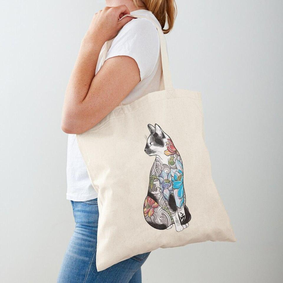 """<p><strong>runcatrun</strong></p><p>redbubble.com</p><p><strong>$16.81</strong></p><p><a href=""""https://go.redirectingat.com?id=74968X1596630&url=https%3A%2F%2Fwww.redbubble.com%2Fi%2Ftote-bag%2FCat-in-Lotus-Tattoo-by-runcatrun%2F25637172.P1QBH&sref=https%3A%2F%2Fwww.thepioneerwoman.com%2Fholidays-celebrations%2Fgifts%2Fg32816249%2Fgifts-for-cat-lovers%2F"""" rel=""""nofollow noopener"""" target=""""_blank"""" data-ylk=""""slk:Shop Now"""" class=""""link rapid-noclick-resp"""">Shop Now</a></p><p>If you know a cat fan who's also into all things floral, this tote bag is for them.</p>"""