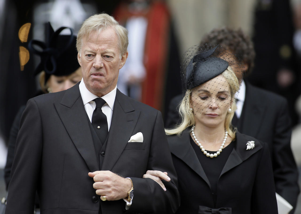 Mark Thatcher and his wife Sarah leave after the ceremonial funeral service for former British Prime Minister Margaret Thatcher in London, Wednesday, April 17, 2013. Thatcher, who died, at the age of 87 on 8 April, has been accorded a ceremonial funeral with military honours, one step down from a state funeral, Thatcher was elected Prime Minister on May 4, 1979 and she resigned on Nov. 28, 1990, after eleven years in office. (AP Photo/Alastair Grant)