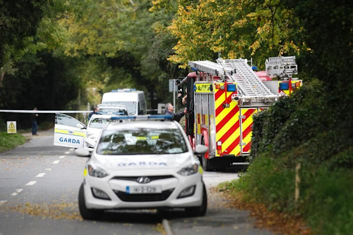 A police officer talks with a fireman at the police cordon in the south Dublin suburb of Carrickmines on October 10, 2015 (AFP Photo/)
