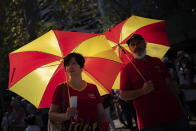 Two demonstrators hold umbrellas decorated with the colours of the Spanish flag during a celebration for Spain's National Day in Barcelona, Spain, Tuesday, Oct. 12, 2021. Spain commemorates Christopher Columbus' arrival in the New World and also Spain's armed forces day. (AP Photo/Joan Mateu Parra)