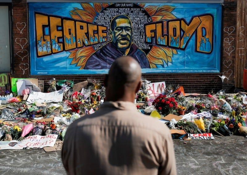 A local resident stands in front of a makeshift memorial honoring George Floyd, at the spot where he was taken into custody, in Minneapolis, Minnesota, U.S., June 1, 2020. REUTERS/Carlos Barria