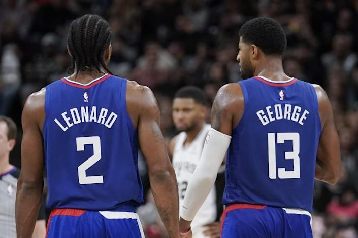 Los Angeles Clippers' Kawhi Leonard (2) and Paul George walk downcourt during the second half of an NBA basketball game against the San Antonio Spurs, Friday, Nov. 29, 2019, in San Antonio. San Antonio won 107-97. (AP Photo/Darren Abate)