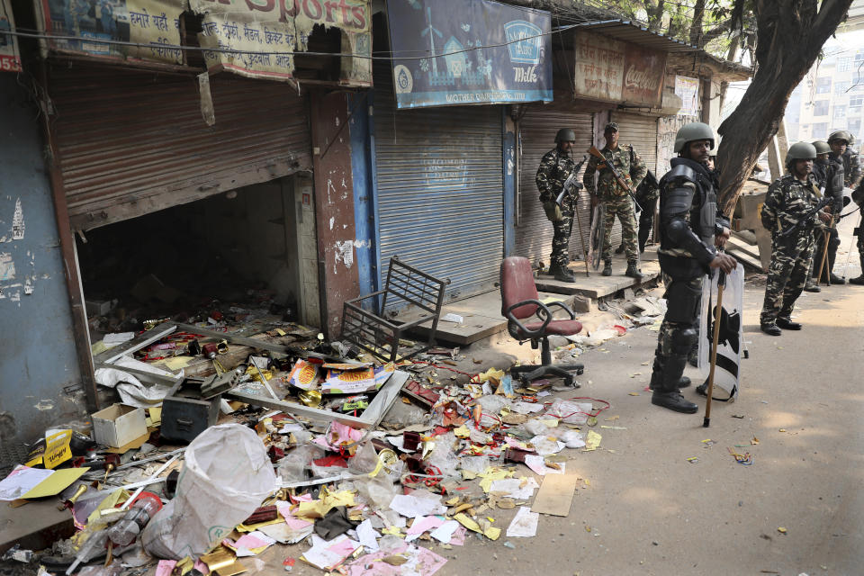 Indian paramilitary soldiers stand guard near a shop vandalised during Tuesday's violence in New Delhi, India, Wednesday, Feb. 26, 2020. At least 20 people were killed in three days of clashes in New Delhi, with the death toll expected to rise as hospitals were overflowed with dozens of injured people, authorities said Wednesday. The clashes between Hindu mobs and Muslims protesting a contentious new citizenship law that fast-tracks naturalization for foreign-born religious minorities of all major faiths in South Asia except Islam escalated Tuesday. (AP Photo/Manish Swarup)