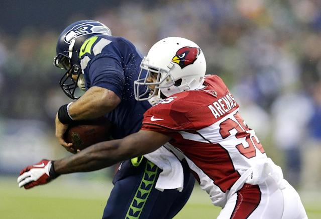 Seattle Seahawks quarterback Russell Wilson, left, is sacked by Arizona Cardinals' Javier Arenas in the second half of an NFL football game, Sunday, Dec. 22, 2013, in Seattle. The Cardinals won 17-10. (AP Photo/Elaine Thompson)