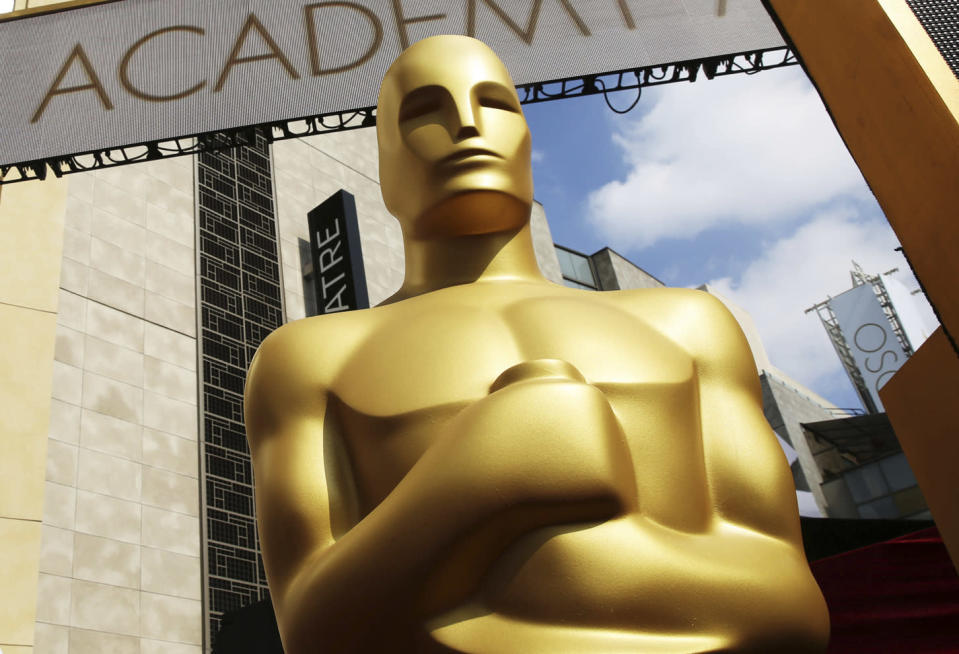 FILE - In this Feb. 21, 2015 file photo, an Oscar statue appears outside the Dolby Theatre for the 87th Academy Awards in Los Angeles. Some people watch awards shows out of love, others because they love to hate. But this year, as ratings have taken a dive, will anybody tune in to the Oscars? Pushed by the pandemic from its usual berth of February or early March, the Academy Awards will be presented April 25 on ABC. (Photo by Matt Sayles/Invision/AP, File)