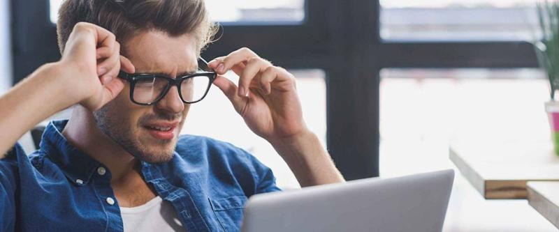 man feeling depressed while looking into laptop