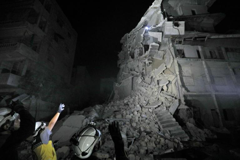 Rescue workers search for victims in the debris of a building after a reported air strike on the town of Ariha, in the south of Syria's Idlib province on July 31, 2019 (AFP Photo/Omar HAJ KADOUR)
