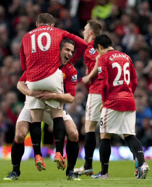 Manchester United's Robin van Persie, centre, celebrates with teammate Wayne Rooney after scoring his second goal against Aston Villa during their English Premier League soccer match at Old Trafford Stadium, Manchester, England, Monday, April 22, 2013. (AP Photo/Jon Super)
