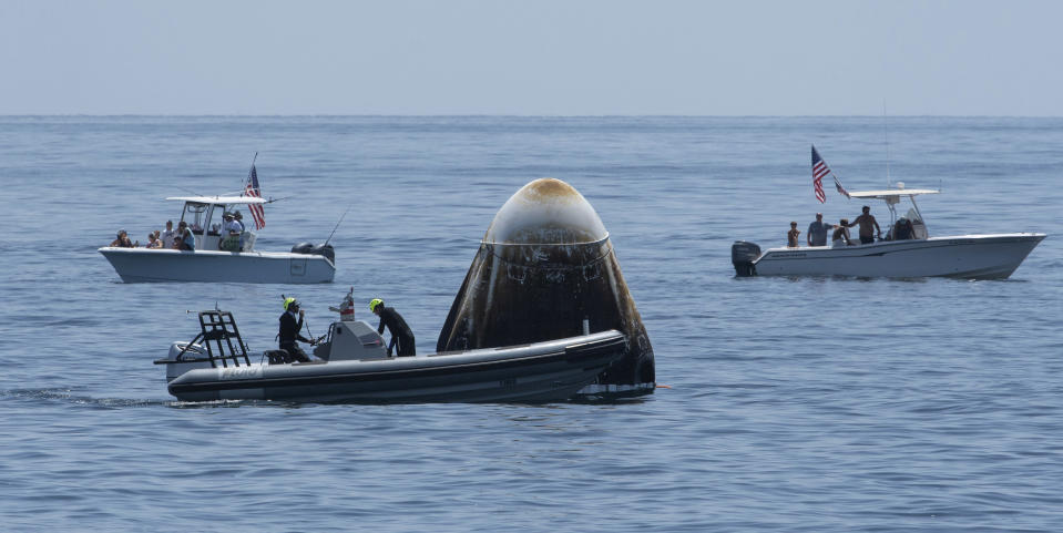 FILE - In this Sunday, Aug. 2, 2020, file photo, provided by NASA, support teams and curious recreational boaters arrive at the SpaceX Crew Dragon Endeavour spacecraft shortly after it landed with NASA astronauts Robert Behnken and Douglas Hurley on board in the Gulf of Mexico off the coast of Pensacola, Fla. The Demo-2 test flight for NASA's Commercial Crew Program was the first to deliver astronauts to the International Space Station and return them safely to Earth onboard a commercially built and operated spacecraft. Behnken and Hurley returned after spending 64 days in space. (Bill Ingalls/NASA via AP, File)