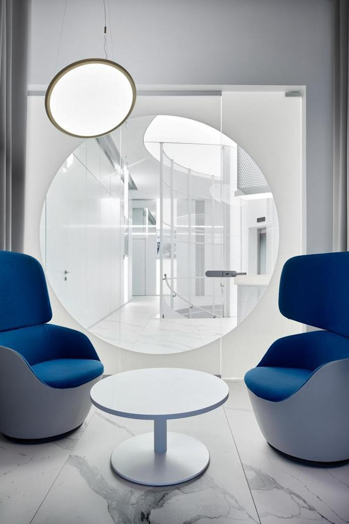 A more private meeting room inside the VIP lounge, complete with wide blue seating and lots of circular decor pieces.