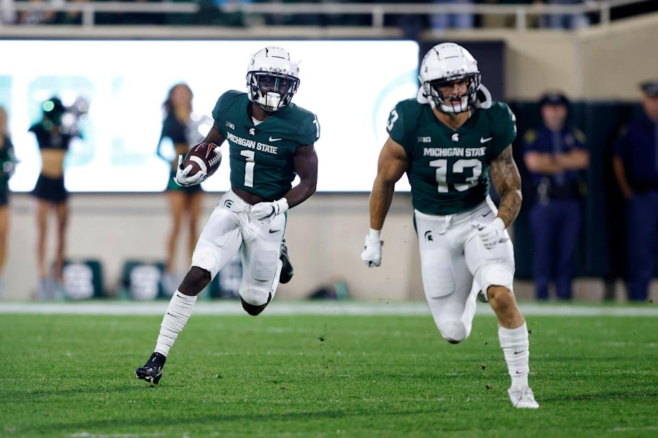 Michigan State's Jayden Reed, left, returns a punt for a touchdown as teammate Ben VanSumeren (13) blocks against Western Kentucky during the first quarter of an NCAA college football game, Saturday, Oct. 2, 2021, in East Lansing, Mich.