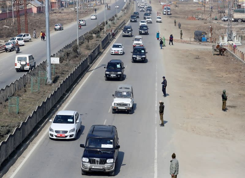 Indian policemen stand guard as a convoy carrying foreign diplomats moves on a road in Srinagar