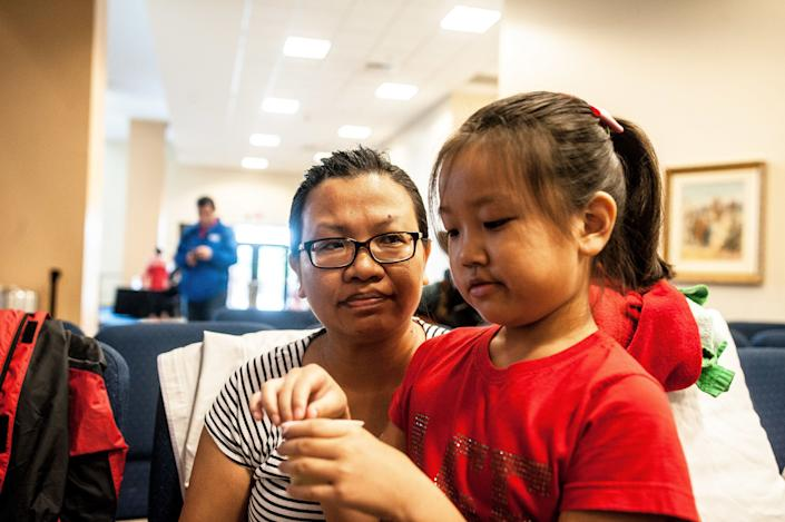 Jie Zhang, 38, and her daughter Sheryl, 8, wait to be entered into the shelter at Lakewood Church in Houston. (Photo: Joseph Rushmore for HuffPost)