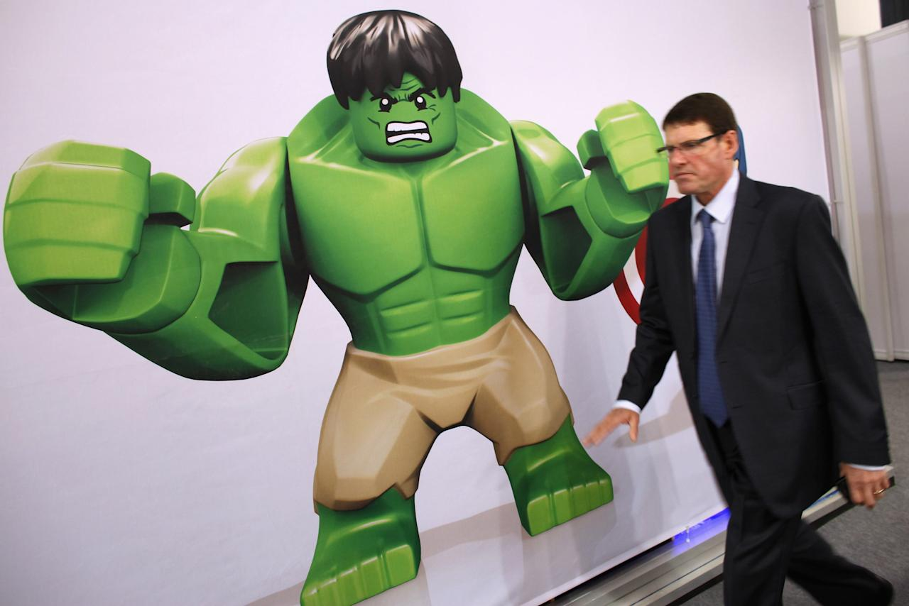 "LONDON, ENGLAND - JANUARY 24:  A man walks past an advertisement for a Lego ""Hulk"" character at the 2012 London Toy Fair at Olympia Exhibition Centre on January 24, 2012 in London, England. The annual fair, which is organised by the British Toy and Hobby Association, brings together toy manufacturers with retailers from around the world.  (Photo by Oli Scarff/Getty Images)"