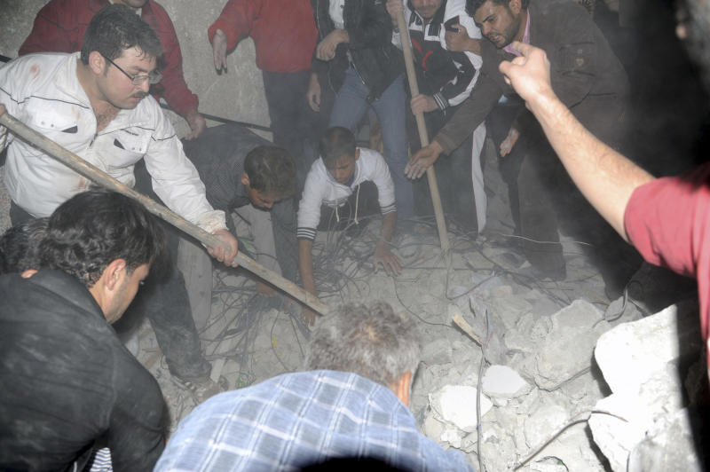 In this image released by the Syrian official news agency SANA , rescuers dig beneath the shattered facade of a building damaged by a car bomb in Damasus, Syria Friday Oct 26 2012. The blast in a residential area of Damascus, near a housing complex for police, killed five people and wounded more than 30, state TV said. A shaky holiday truce was marred by sporadic fighting and two car bombs Friday but gave war-battered Syrians a brief respite, allowing thousands of protesters to pour out of mosques to demand President Bashar Assad's ouster.(AP Photo/ Sana)