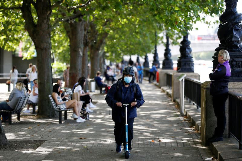 FILE PHOTO: A woman wearing a protective face mask rides a scooter along the South Bank, amid the spread of coronavirus disease (COVID-19), in London