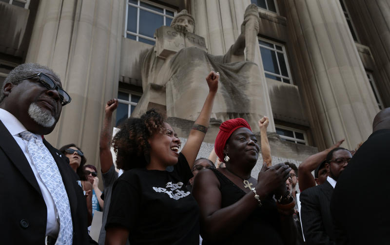 LaShell Eikerenkoetter, center, and Julia Davis cheer the words of area clergy who called for a guilty verdict in the shooting death of Anthony Lamar Smith by former St. Louis police Officer Jason Stockley. (Robert Cohen/St. Louis Post-Dispatch via Getty Images)
