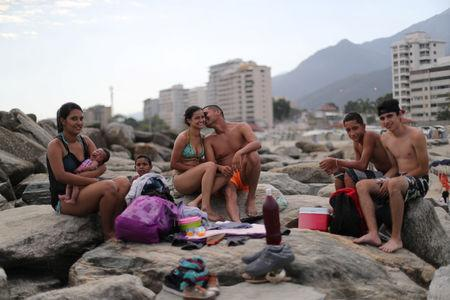 """Leonel Martinez, who works as soldier, kisses his girlfriend as they spend a day at Coral beach in La Guaira near Caracas, Venezuela, March 23, 2019. """"It's a way to think about something besides what is happening in the country,"""" said Martinez. """"It's not something you can do every day, because of the situation in the country.""""   REUTERS/Ivan Alvarado"""