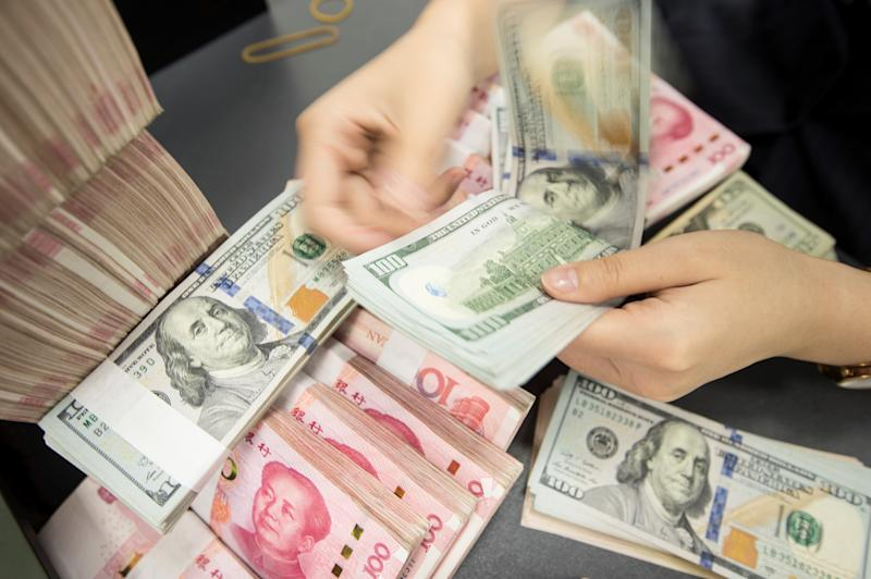 "A Chinese bank employee counts 100-yuan notes and US dollar bills at a bank counter in Nantong in China's eastern Jiangsu province on August 6, 2019. - The Chinese currency steadied on August 6, a day after Beijing let the yuan weaken against the dollar, sending markets into freefall and leading the US to formally designate China a ""currency manipulator"". (Photo by STR / AFP) / China OUT (Photo credit should read STR/AFP/Getty Images)"