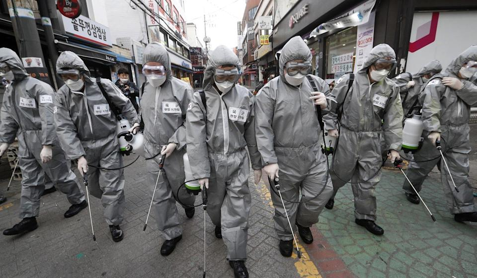 South Korean soldiers wearing protective suits spray disinfectant as a precaution against the new coronavirus at a shopping street in Seoul on Wednesday. Photo: AP
