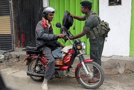 A soldier checks a man on a motorbike outside the Grand Mosque in Negombo, Sri Lanka April 26, 2019. REUTERS/Athit Perawongmetha