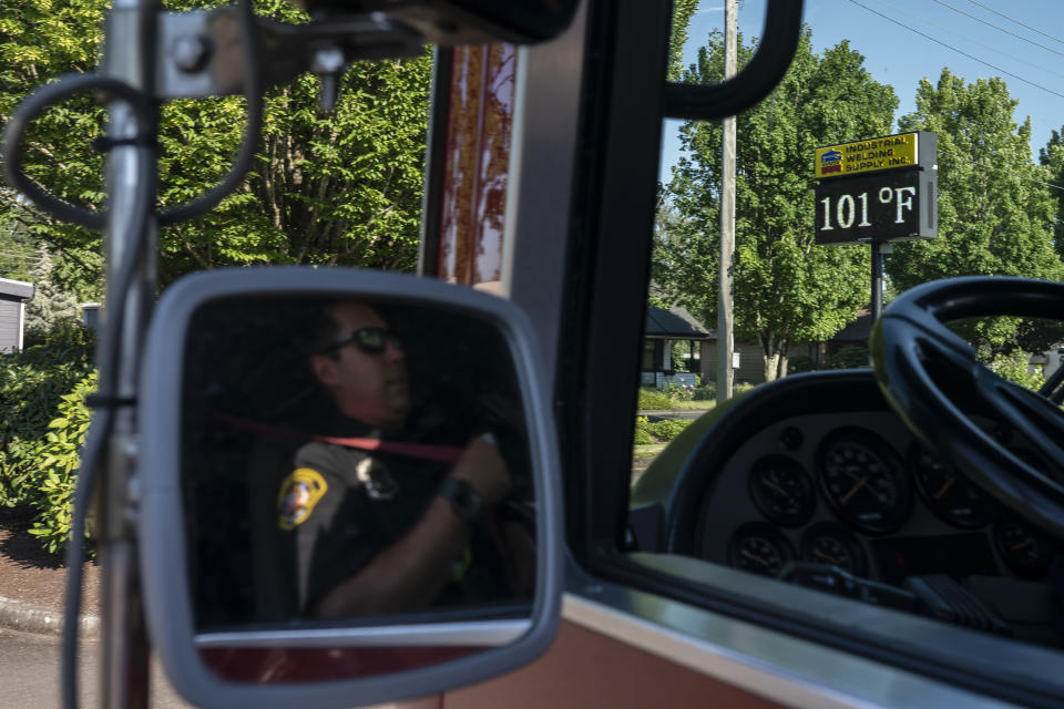 Cody Miller, with the Salem Fire Department, waits in his truck near a digital sign tracking the day's temperatures during a heat wave, Saturday, June 26, 2021, in Salem, Ore. (AP Photo/Nathan Howard)
